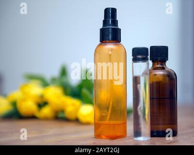 Colourful plastic transparent bottles for spa procedures at home and towels on wooden table. Recycling plastic bottles and flasks. Handmade essentia - Stock Photo
