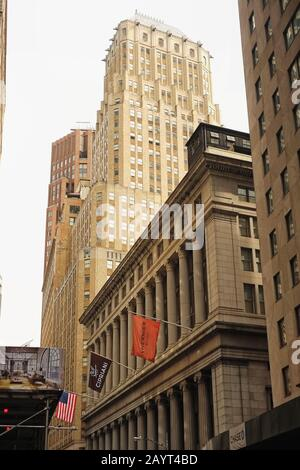 National City Bank Building -  Merchants' Exchange at 55 Wall Street in Greek Revival style and 67 Wall Street  an stylish art deco skyscraper behind - Stock Photo