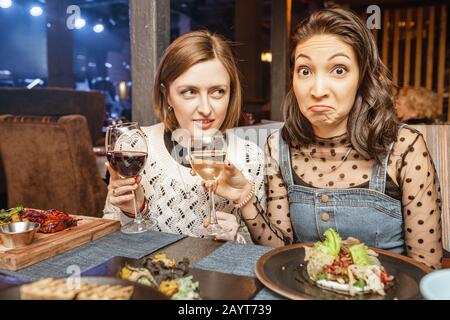 Two girls friends chatting and drinking wine in a restaurant in a nightclub. Concept of friendship and food and drinks - Stock Photo