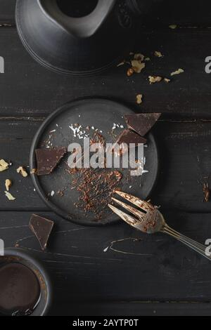 Black empty plate with cake leftovers from above on wooden background - Stock Photo