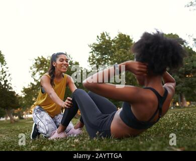 Young sporty fit active female friends doing sits-up on green grass in the park