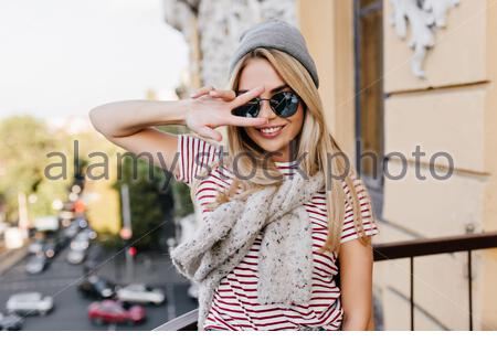 Ecstatic female model with tanned skin fooling around at balcony in morning. Portrait of attractive blonde girl in hat posing with peace sign and smiling. - Stock Photo