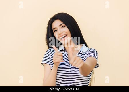 Shot of attractive European female gives double thumb up, has positive expression, has white teeth with brackets, dressed casually, makes okay and app - Stock Photo