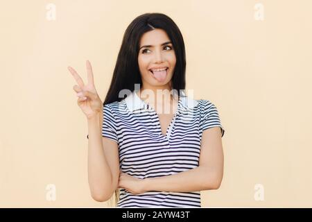 Positive funny female makes peace sign with hand, shows tongue, being in good mood, has long dark hair, has healthy skin, wears casual clothes, isolat - Stock Photo