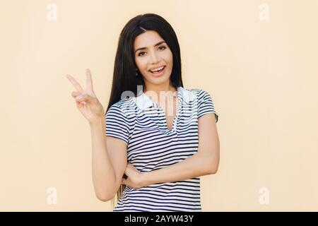 Portrait of cheerful brunette female with joyful expression, makes peace sign with two fingers, dressed casually, isolated over beige background. Beau - Stock Photo