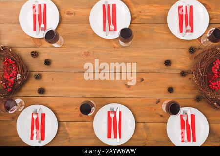 On the table lie cones, wreaths. Festive table set for six people. Wooden background top view mock-up. Wooden background top view mock-up - Stock Photo