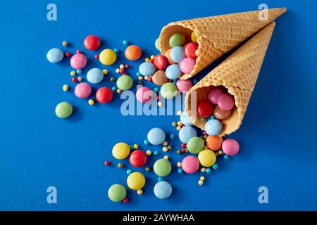Party background with colorful sugar-coated chocolate candy scattered over blue and wafer ice-cream cones in a flat lay still life with copy space - Stock Photo