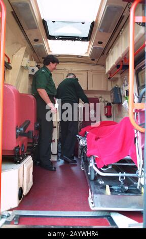 Two paramedics attend to a patient in the back of an ambulance Stock Photo