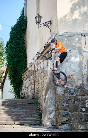 Side snapshot of a stuntman getting ready to jump with his mountain bike from the corner of ancient building - Stock Photo