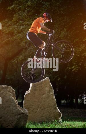 Extreme show of talented trail biker performing on big rocks standing on back wheel, in the evening in park, side view snapshot, concept of active lifestyle - Stock Photo