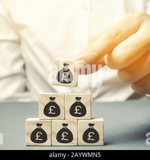 Businessman puts wooden blocks with the image of money. Business concept. Profit, finance and budget management. Planning. Distribution of funds. Capi Stock Photo
