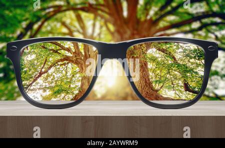 Vision concept. Eye glasses on wooden table. 3d rendering - Stock Photo