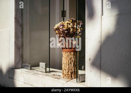 Arrangement of dried flowers in a wooden vase - Stock Photo