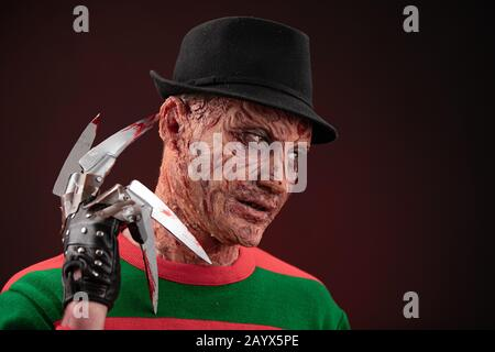 portrait of a man with a scary face and metal claws. Grimm hero for a horror movie. Freddy Krueger. 06 February 2020 Ukraine, Kyiv. make-up - Stock Photo