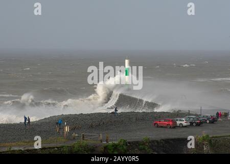 Stormy weather creates big waves that smash into Aberystwyth, Wales while onlookers are dwarfed by the size of the waves. - Stock Photo
