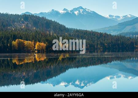 Snowy mountains reflected in Gun Lake in British Columbia, Canada - Stock Photo