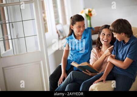 Portrait of woman reading a story to her son and daughter. - Stock Photo
