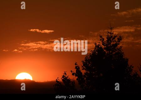 Bright Sun Rising Over Dramatically Silhouetted Mountain Ridge Against Orange Cloudy Sky - Stock Photo