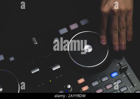 DJ plays music. sound mixer controller with knobs and sliders close up. hands on the mixing deck with turntables at dark with illuminated controls - Stock Photo