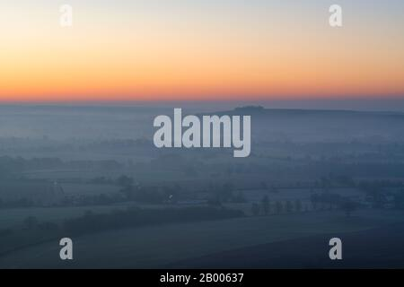 View from Martinsell Hill on a foggy winter morning at sunrise. Near Oare, Vale of Pewsey, Wiltshire, England - Stock Photo