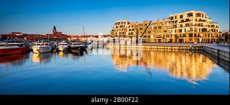 City harbour with modern hotel complex in the evening light, church St. Marien in the back, Waren an der Mueritz, Mecklenburg Lake District - Stock Photo