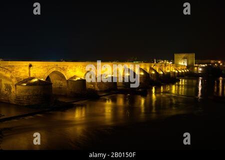 Illuminated Roman bridge, across Guadalquivir river with Torre de Calahorra, Calahorra Tower in Cordoba, Andalusia, Spain - Stock Photo