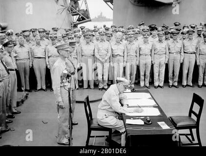 General Douglas MacArthur signs as Supreme Allied Commander during formal surrender ceremonies on the USS Missouri in Tokyo Bay. Behind General MacArthur are Lieutenant General Jonathan Wainwright and Lieutenant General A. E. Percival.  On August 28, the occupation of Japan by the Supreme Commander of the Allied Powers began. The surrender ceremony was held on September 2 aboard the U.S. battleship Missouri, at which officials from the Japanese government signed the Japanese Instrument of Surrender, ending World War II. - Stock Photo