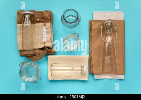 Set of textile eco bags, paper packages and glass jars lying on blue background. Eco friendly, reuse or zero waste concept. Top view. Flat lay