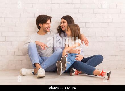 Cheerful mom, dad and their little daughter sitting near white wall - Stock Photo