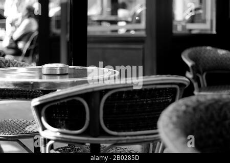 Classic French Cafe Black and White View. Iconic Parisian Cafe Terrace with Wicker Chairs. - Stock Photo