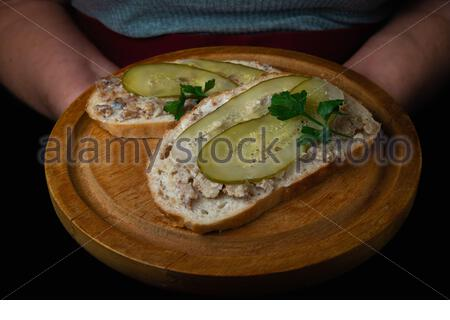 Polish style bread with lard and cucumber on a wooden plate held by a waitress in a red apron - Stock Photo