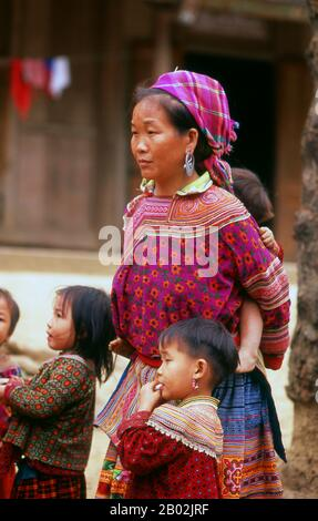 The hills around Bac Ha are home to ten separate minorities, including Dao, Giay, Nung and Tai, but the most distinctive and colourful are the Flower (Flowery) Hmong. From before dawn they converge on Bac Ha's dusty town centre and, especially, the concrete market. Goods sold and exchanged include fruit and vegetables of every description, fresh meat and wild orchids.  The Hmong are an Asian ethnic group from the mountainous regions of China, Vietnam, Laos, and Thailand. Hmong are also one of the sub-groups of the Miao ethnicity in southern China. Hmong groups began a gradual southward migrati - Stock Photo