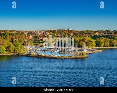 A view of the island of Lidingo, Stockholm, Sweden, from the water, with houses in a green landscape and a marina, an example of the Swedish lifestyle - Stock Photo