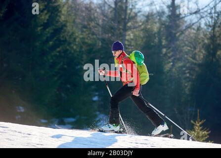 Man alone with ski in the mountain. Guy with a backpack on a blurred background of forest at sunny day. Ski season and winter sports concept - Stock Photo
