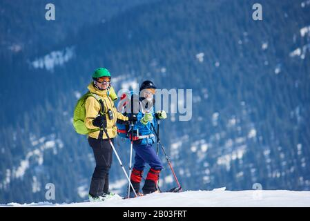 Two male skiers hikers in skiing equipment with backpacks on skis on background of mountain snowy slope covered with green spruce trees on frosty day. Winter tourism, ecological holidays concept. - Stock Photo