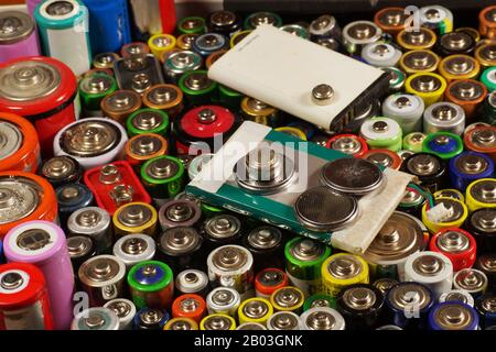 Preparations for recycling or utilization. Dozens of types, sizes, colors of used batteries and accumulators. - Stock Photo