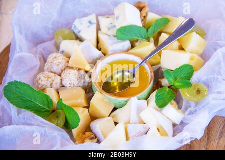 Plate with different types of cheese on white paper with honey decorated with green mint leaves - Stock Photo
