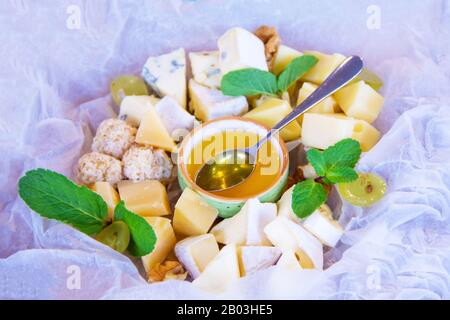 a lot of types of cheese Parmesan, Gouda, Emmental cheese with honey, walnuts and physalis. appetizer in a French restaurant, snack for wine. dish for - Stock Photo