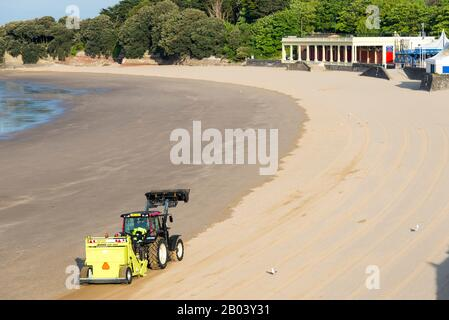 Whitmore Bay beach at Barry Island, Wales,early on a bright sunny summer morning being cleaned of litter by a red Tractor pulling a Barber Surf Rake. - Stock Photo