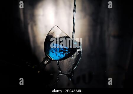 Blue drink being spilled from glass. Low key dark photo. Drink being poured into glass, but missing it. - Stock Photo