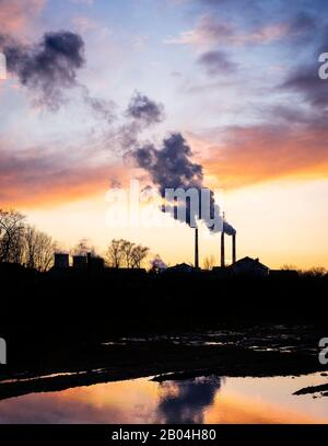 Cogeneration plant on the outskirts of a big city.  Smoke from the chimneys at sunset. Metaphor of human impact on the environment, carbon emissions.