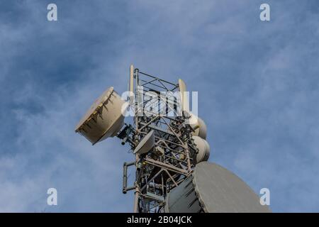 A telecommunications tower top against the background of the clear blue sky - Stock Photo