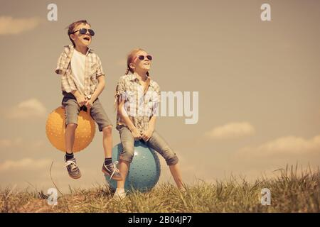 Brother and sister playing on the field at the day time. Children having fun outdoors. They jumping on inflatable balls on the lawn. Concept of friend - Stock Photo