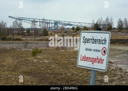 06 February 2020, Brandenburg, Lichterfeld: A sign 'Sperrbereich - Betreten verboten - Lebensgefahr' (restricted area - no trespassing - danger to life) stands in front of the former overburden conveyor bridge F60 is in the former opencast lignite mine Klettwitz-Nord. The conveyor bridge is now used as an accessible visitor mine. Photo: Gregor Fischer/dpa - Stock Photo