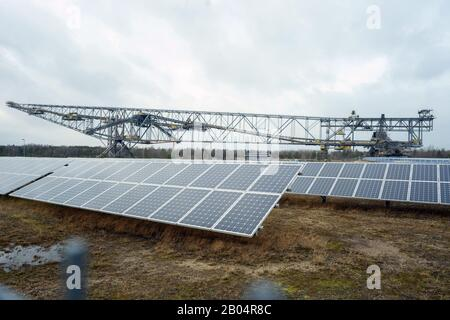 06 February 2020, Brandenburg, Lichterfeld: Solar plants are located in front of a former overburden conveyor bridge 'F60' in a visitor mine of the former opencast lignite mine Klettwitz-Nord. Photo: Gregor Fischer/dpa - Stock Photo