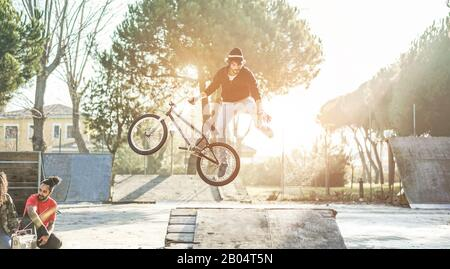 Group of friends watching a biker performing freestyle jump with bmx bicycle - Young people having fun with extreme sport recreation in urban city par