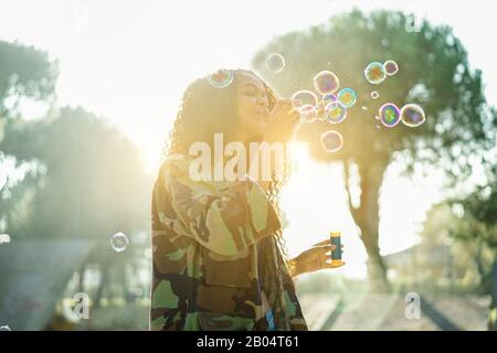 Young afro hair woman blowing soap bubble in city skate park with back sun light - Portrait of african happy girl having fun outdoor - Happiness conce