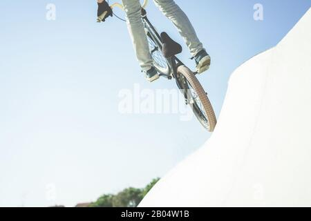 Bmx biker jumping in city skate park outdoor - Young trendy man performing skills and tricks with special bicycle - Extreme sport concept - Focus on b