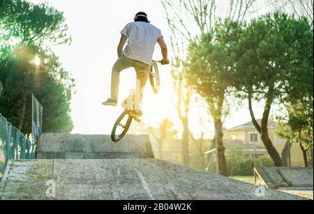 Biker jumping in bmx pro jump session outdoor in city urban park with back light - Young man making extreme sport at sunset - Danger activity concept