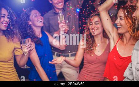 Happy friends making party throwing confetti, dancing and drinking champagne inside nightclub - Entertainment, fun, new year's eve, nightlife, concept - Stock Photo